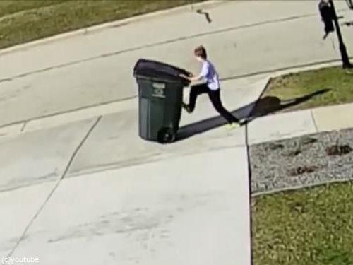 強風に吹き飛ばされかけながらゴミ箱を運ぶ少年02