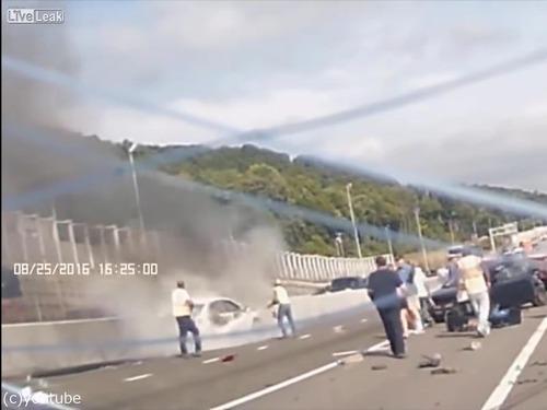 事故で燃える車から女性を救出する人々06