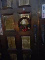 クリスマスリースの付いた扉のガラス窓から覗くレディ子