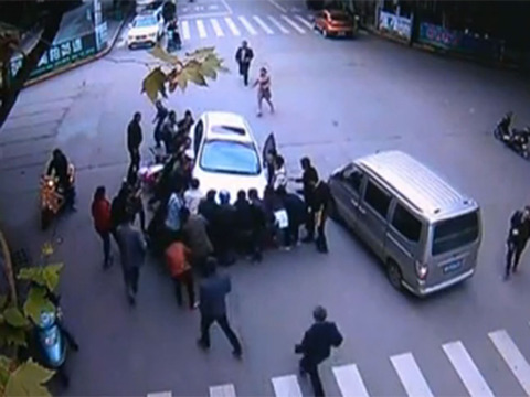 v2-Crowd in China lifts a car off woman following crash