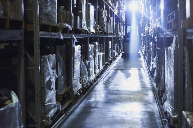 focused_199386476-Back-lit-forklift-distribution-warehouse
