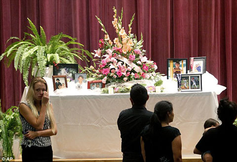 1411490209298_wps_42_Mourners_look_at_a_displa