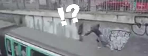 地下鉄の屋根の上に飛び乗る男
