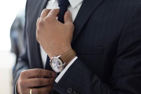 スーツ姿でネクタイを締める人