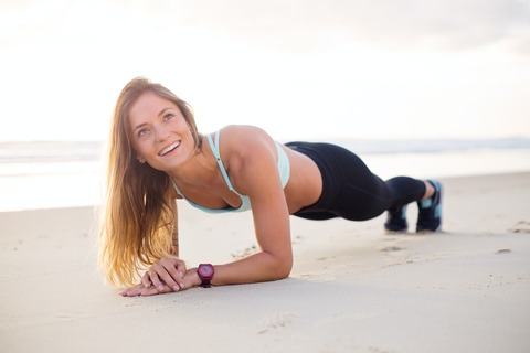 砂浜でプランクを行う女性