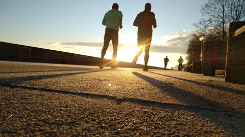 夕陽に向かってジョギングをする男女