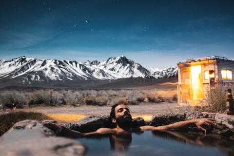 外で温泉に入って疲れを癒す男性