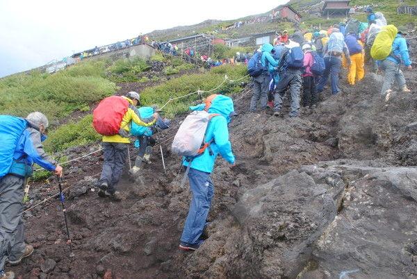 雨の中、渋滞の岩場を歩く。遠くの山小屋まで渋滞の列が伸びている