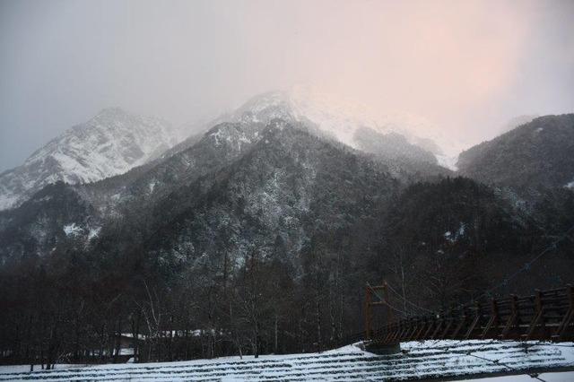白雲に朝日が当たる明神岳