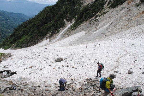 白馬大雪渓の終点。落石が転々と転がっている中を登山者が登って来る
