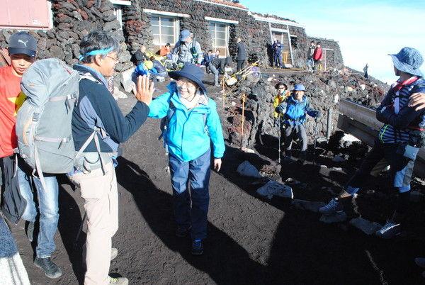 山頂で太田ガイドとハイタッチする参加者
