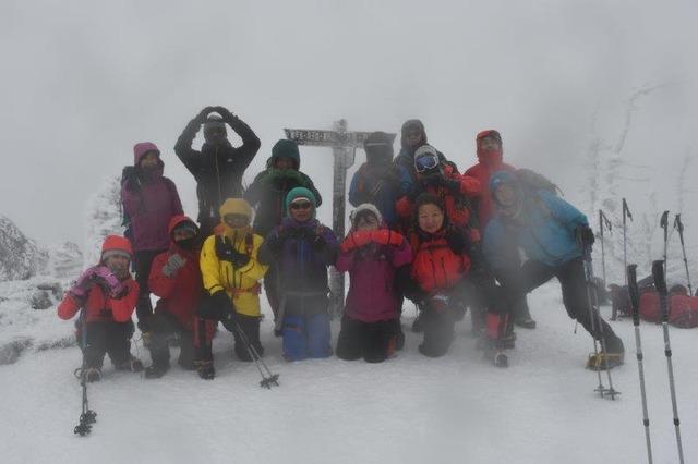 参加者が北横岳山頂で記念撮影。レンズに雪が着いてしまった