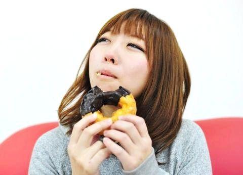 おいしそうにドーナツを食べる女の子