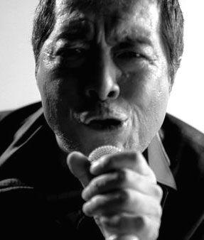 マイクを握って歌っているモノクロの矢沢永吉の画像