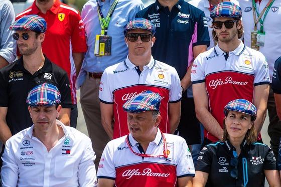 ジャッキー・スチュワートの80歳を祝ってF1ドライバーと関係者の記念写真、参加者全員が彼のトレードマークのタータン・チェック柄のハンチング帽を被っている。