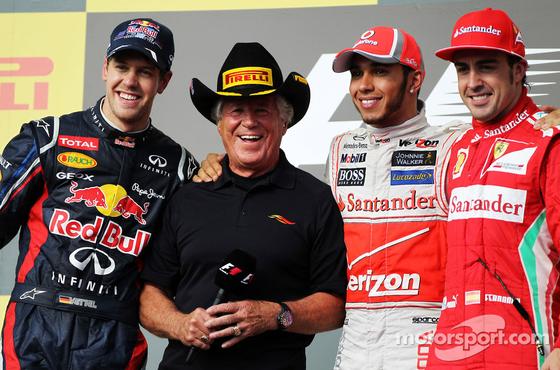 2012年F1アメリカGP 1位ルイス・ハミルトン(マクラーレン)、2位セバスチャン・ベッテル(レッドブル)、3位フェルナンド・アロンソ(フェラーリ)と表彰台インタビュアーのマリオ・アンドレッティ