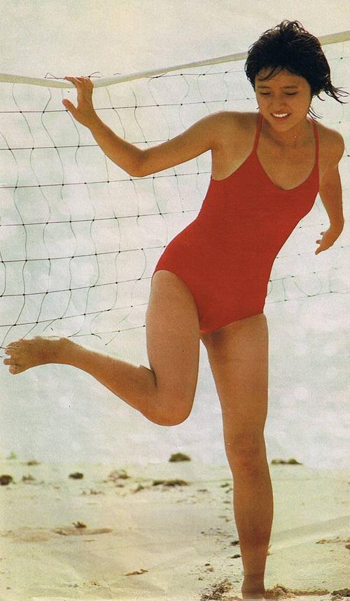 ビーチバレーのネットの前で赤い水着で立つアイドル時代の三田寛子