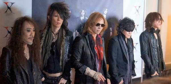 自分たちの写真パネルの前に立って並んでいるX JAPANの画像