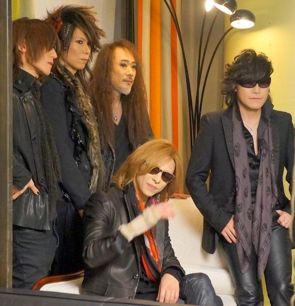 ソファーに座るYOSHIKIとその周りに立っているメンバー4人のX JAPANの画像