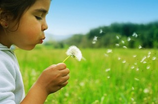 Child-blowing-bloom