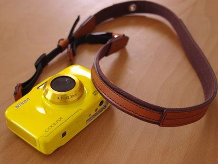 イエローカラーのカメラとレザーのストラップ