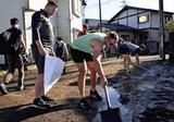 道路に溢れ出た泥を袋に詰めるカナダ代表たち