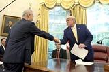 暫定合意を得て握手を交わす両首脳