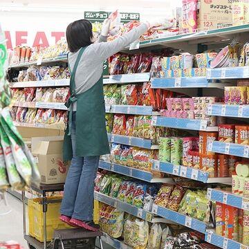 棚に商品を並べる人