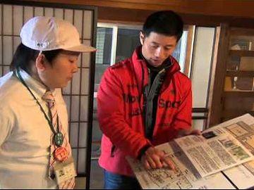 """熱心に説明する白川さん。左の人物は、""""生ゆるキャラ""""こと『おもち君』(なんと、五所川原市観光課の職員です)。"""