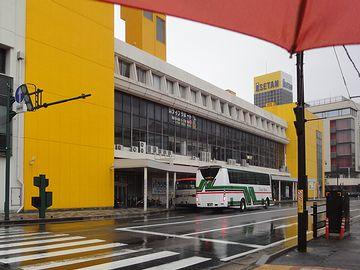 傘の下から、バスセンターを臨む