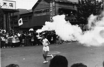 静岡市内を走る聖火ランナー。煙が出すぎだろ。