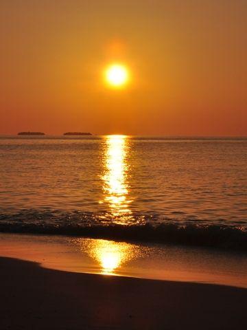 太陽から砂浜まで、赤い絨毯が伸びる