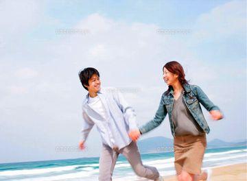 恋人同士が、砂浜を走ってる