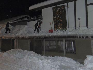 12月末の西田酒造店。午前5時、お店の雪下ろしをする社員さん。