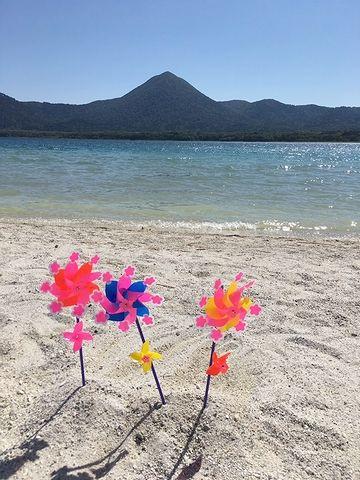 湖の砂浜に、風車が回ってる風景