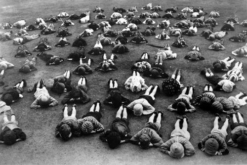 防空頭巾で地面に伏せる子どもたち1943年