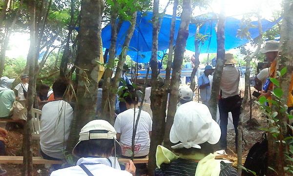 やむを得ず森の中で集会する地元の人と市民