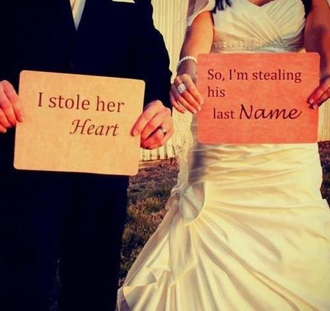 洒落たプラカードを持つ花婿花嫁