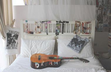 白いダブルベッドにギター