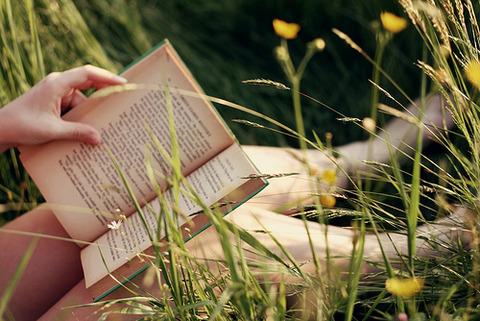 草むらに足を投げ出して本を広げてる女の子の手