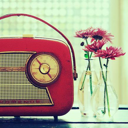左に赤いラジオ、右に2つのガラス瓶に入った赤い花