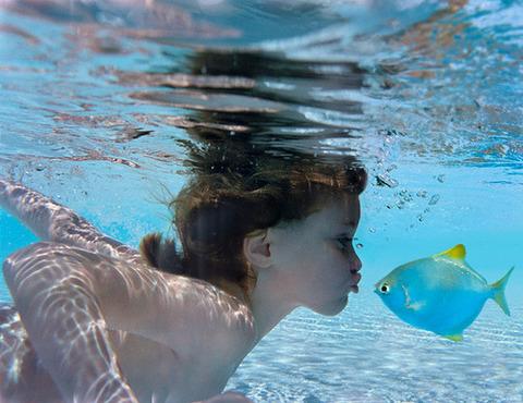 水中で女の子が熱帯魚にキス