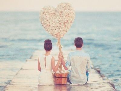 桟橋に座り、大きな薄ピンクの花で出来たハートを持ってる恋人