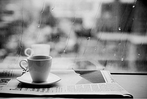 雨の窓辺にコーヒーカップと英字新聞
