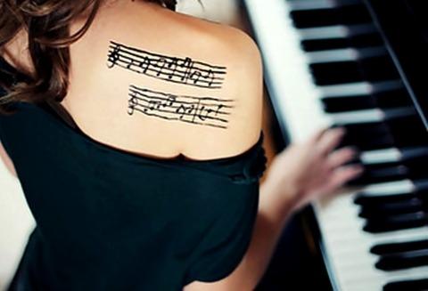 ピアノを弾く女性の右肩に楽譜