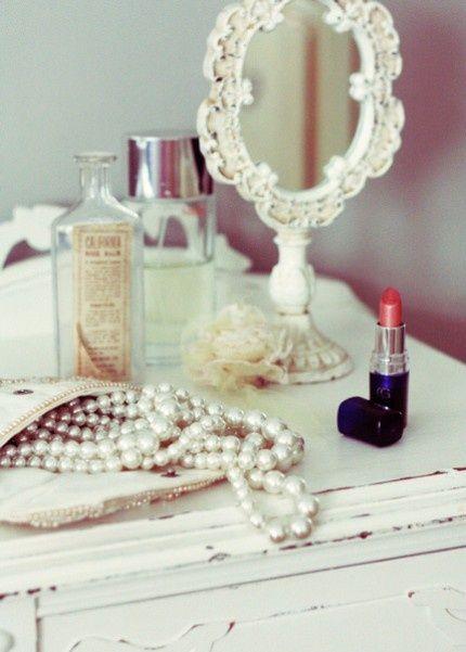 白い卓上手鏡とリップスティックとネックレスと