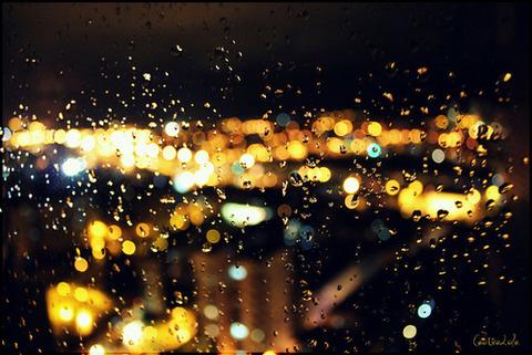 雨のしずくの窓ガラスの向こうに黄色い町の灯