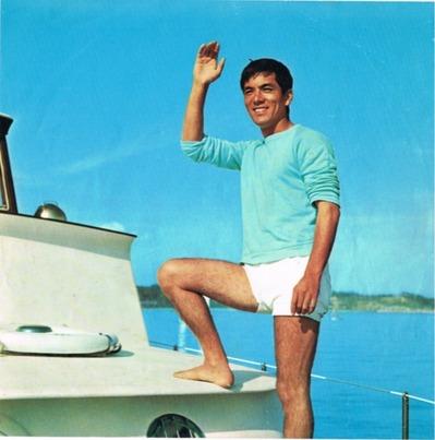 加山雄三 ヨットの上、右手上げ水色のTシャツ