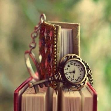 本の上のカギの形をした懐中時計風キーホルダー?