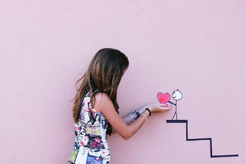 壁に描かれた階段を上った漫画のハートを受け取る女性